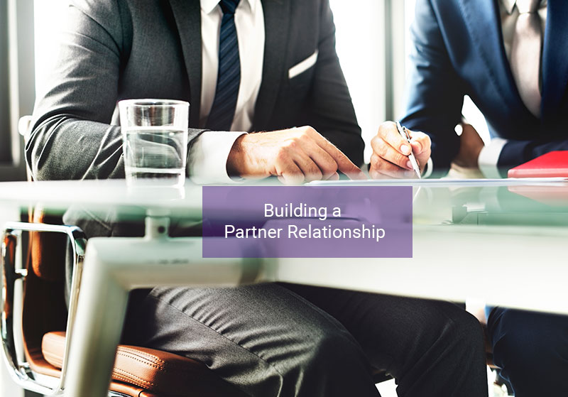 two business men sitting down building a partner relationship